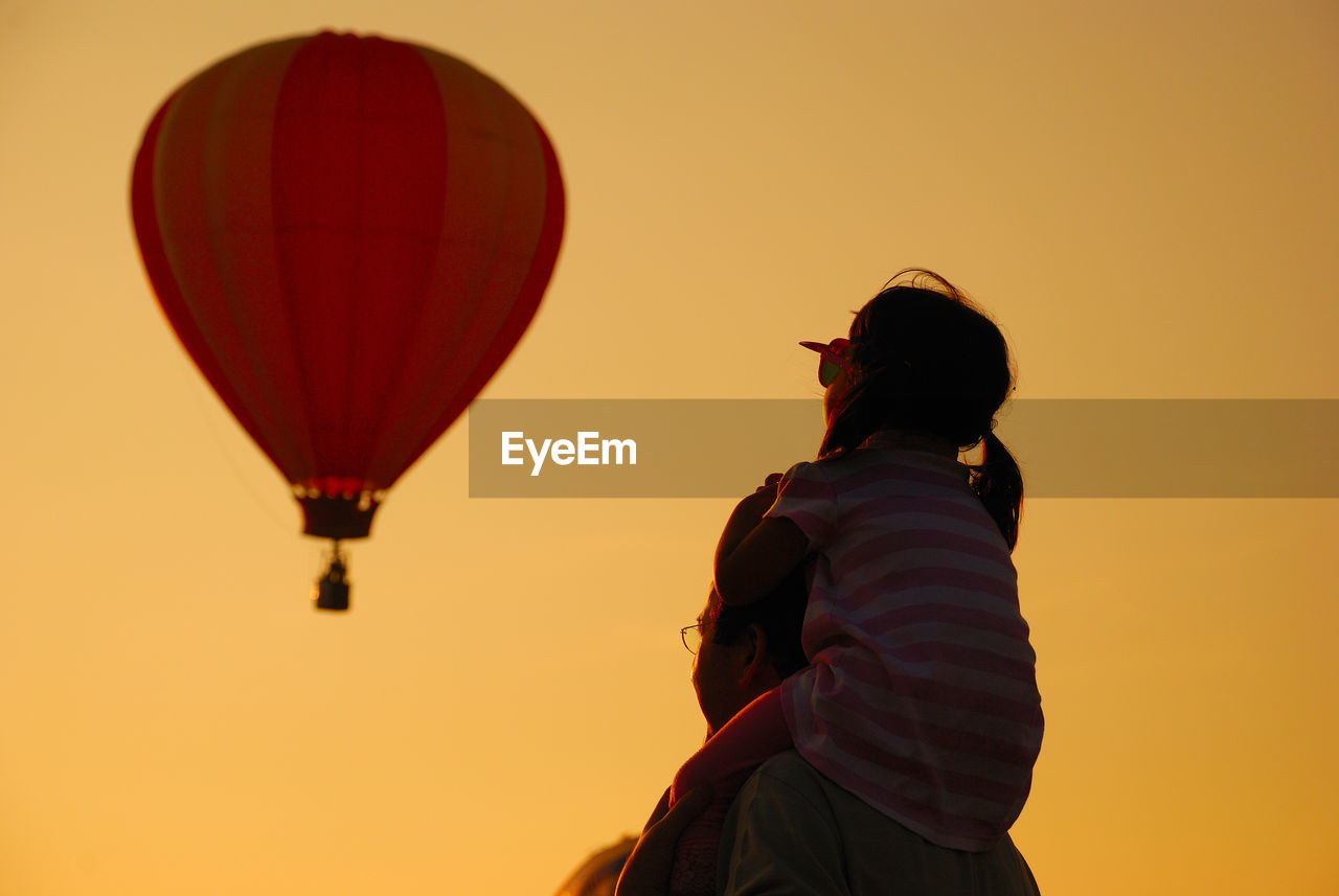 Father Carrying Daughter With Hot Air Balloon Against Clear Sky