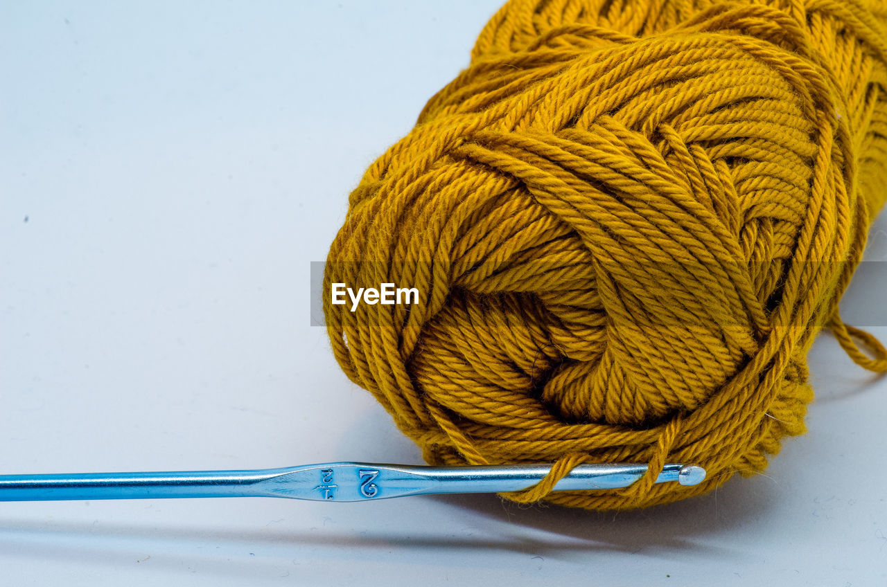 Close-up of yellow wool over white background