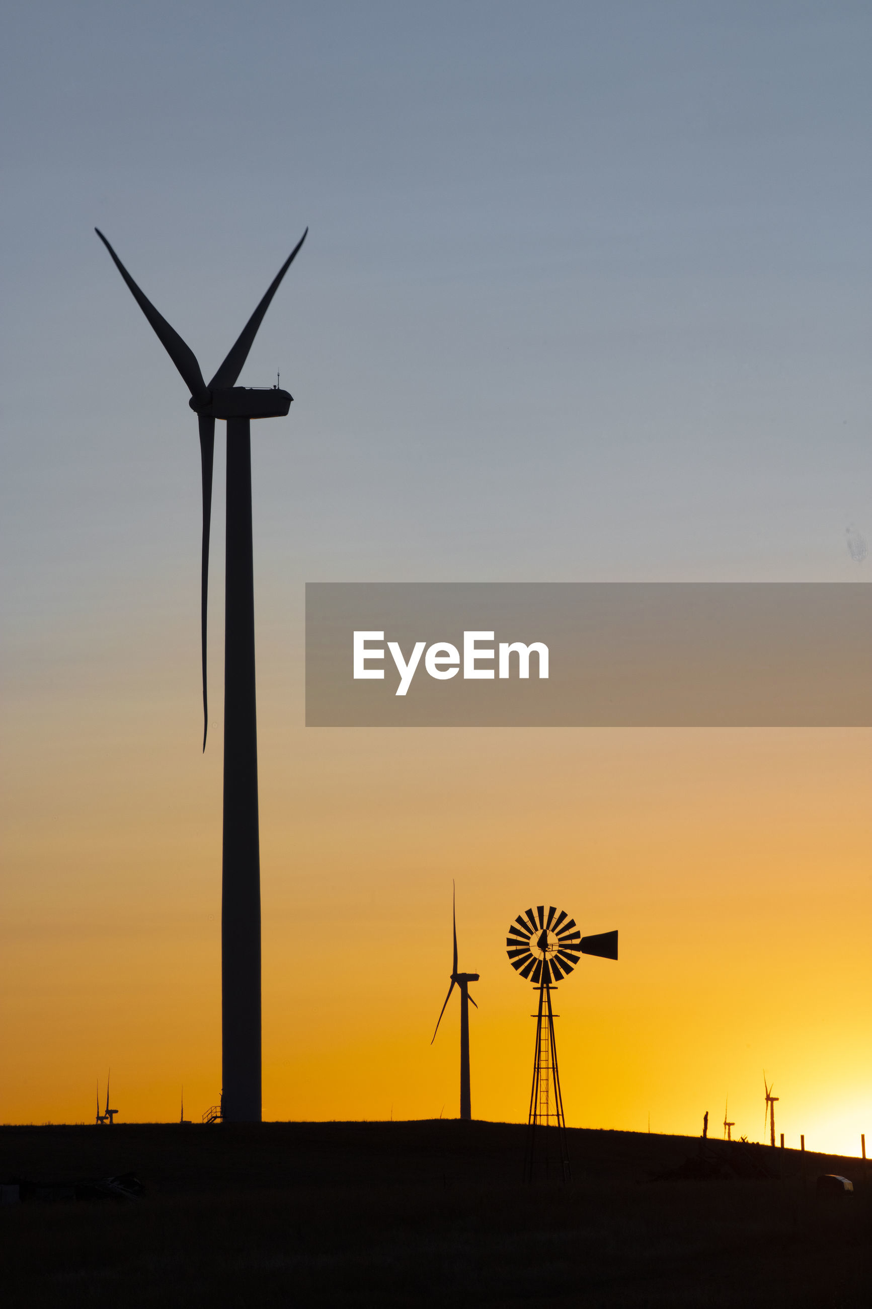 SILHOUETTE WIND TURBINE ON FIELD AGAINST SKY DURING SUNSET
