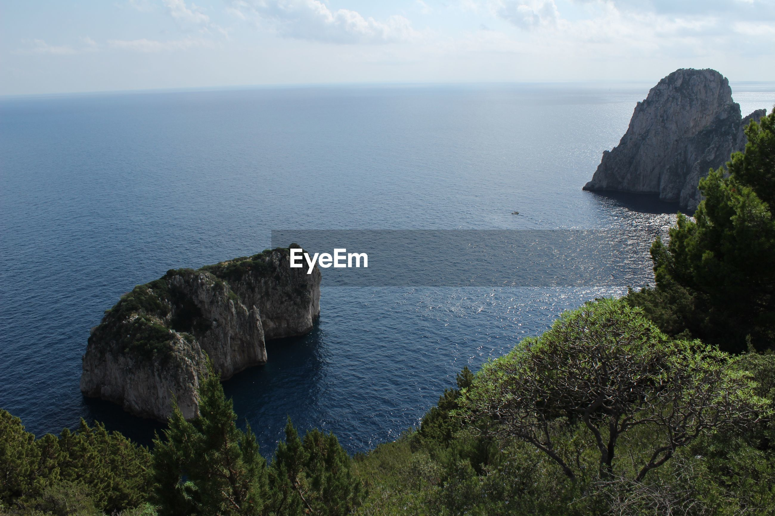 SCENIC VIEW OF ROCK FORMATIONS IN SEA AGAINST SKY