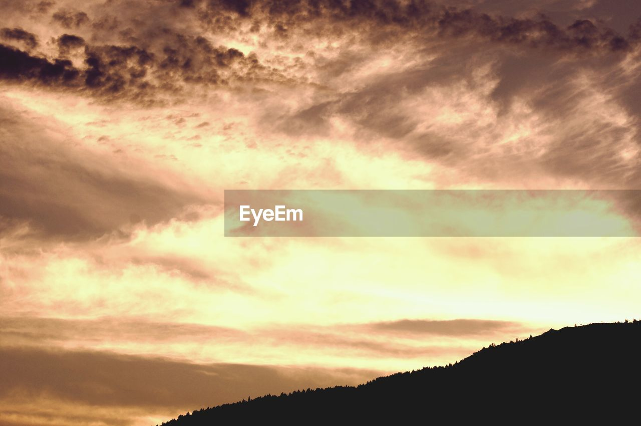 cloud - sky, sky, beauty in nature, silhouette, scenics - nature, sunset, tranquility, tranquil scene, orange color, low angle view, nature, dramatic sky, no people, idyllic, outdoors, environment, mountain, non-urban scene, overcast