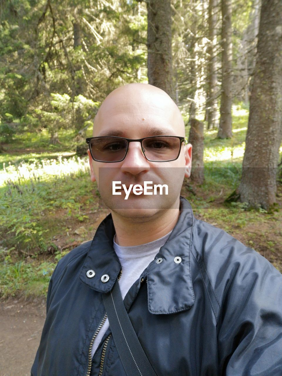 portrait, looking at camera, tree, one person, glasses, plant, real people, lifestyles, sunglasses, headshot, leisure activity, land, front view, smiling, fashion, mid adult, adult, forest, mature adult, mature men, outdoors, leather
