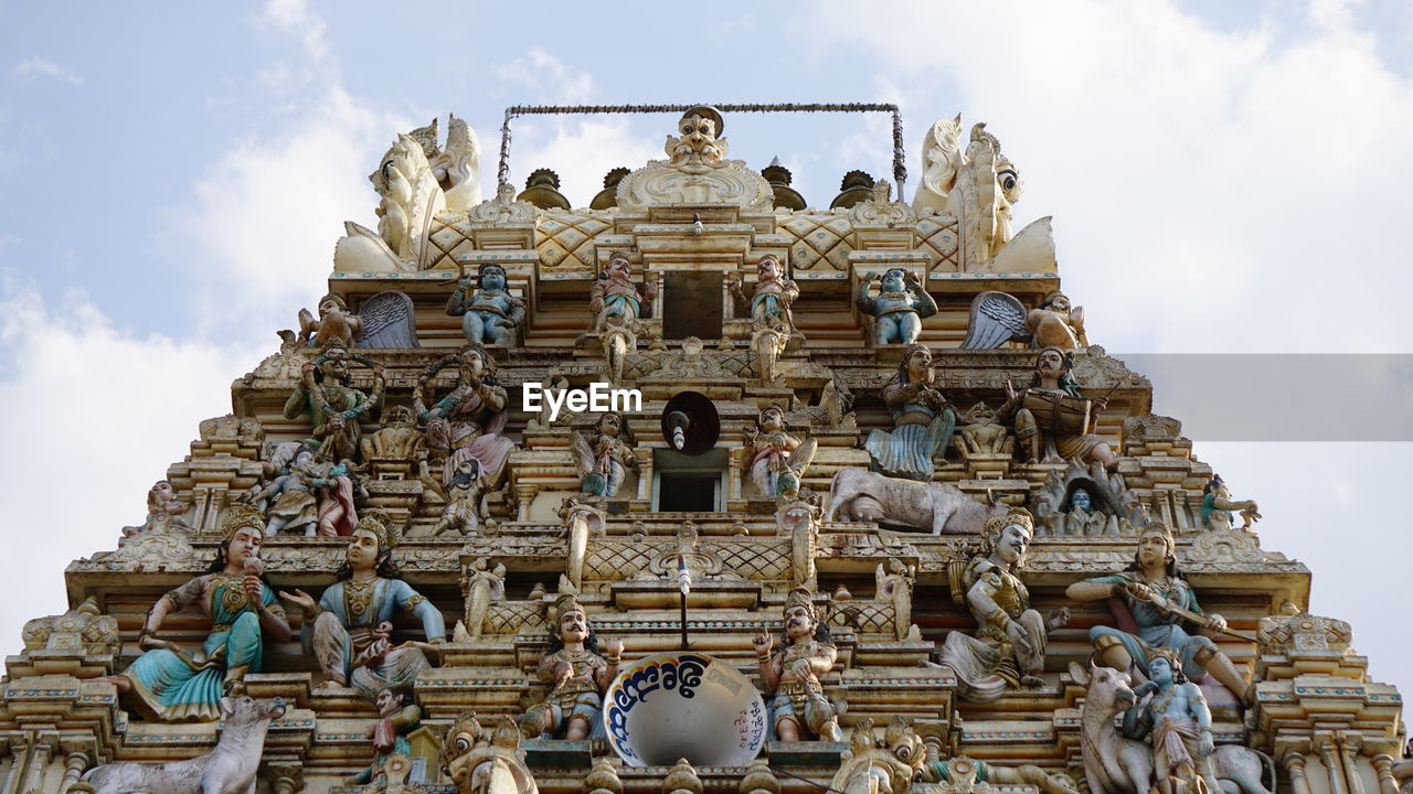 art and craft, belief, sculpture, religion, place of worship, low angle view, spirituality, representation, human representation, creativity, statue, architecture, built structure, craft, travel destinations, sky, male likeness, cloud - sky, no people, ornate