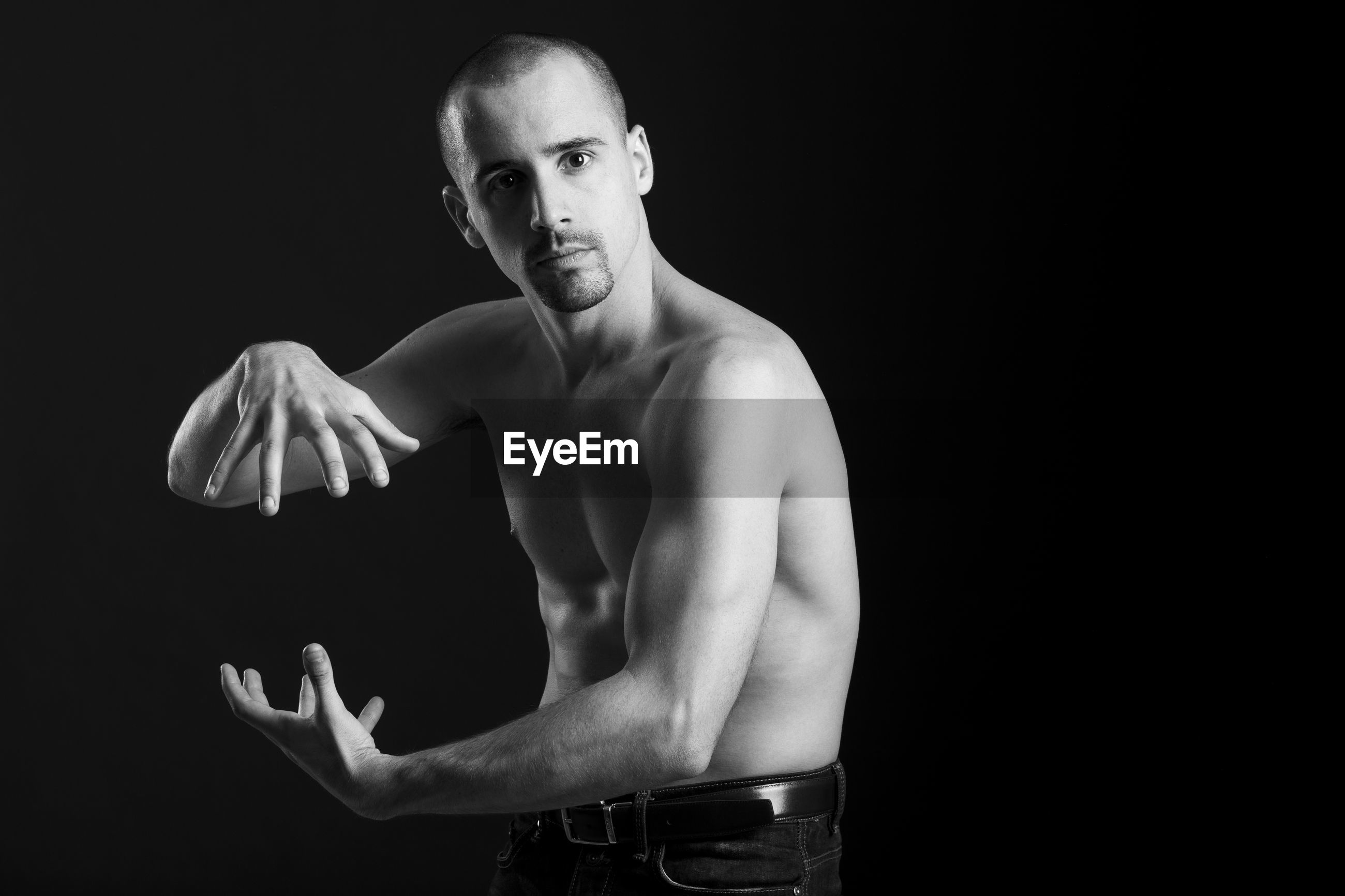 Portrait of shirtless man doing martial arts against black background