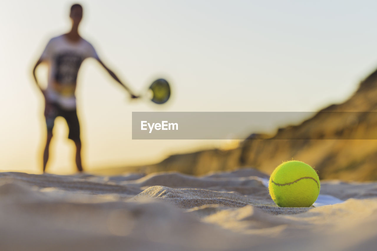 selective focus, ball, close-up, sport, tennis, no people, yellow, tennis ball, representation, still life, day, human representation, sphere, nature, toy, outdoors, sky, sports equipment, green color, figurine, surface level