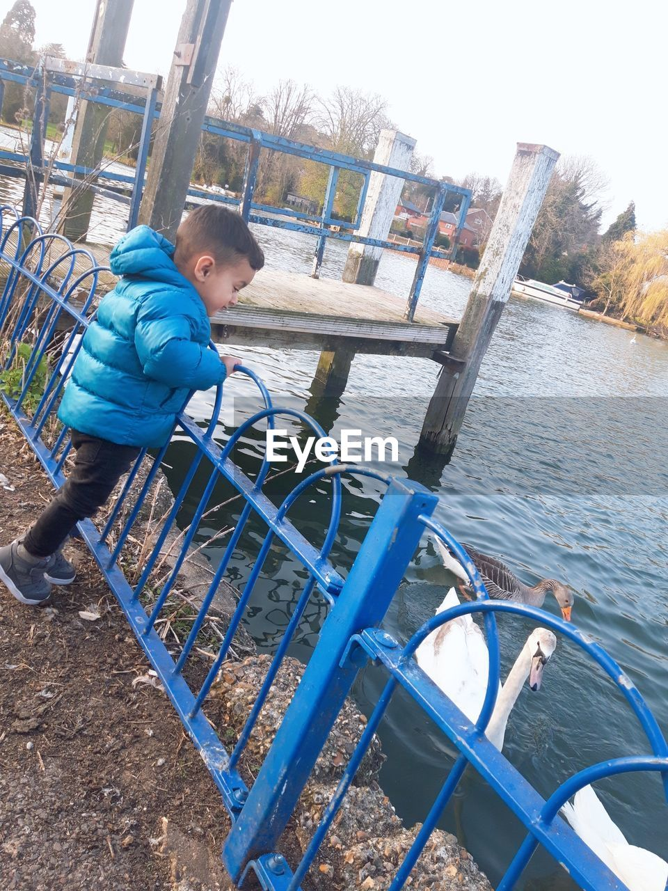Side view of boy wearing warm clothing while standing by lake