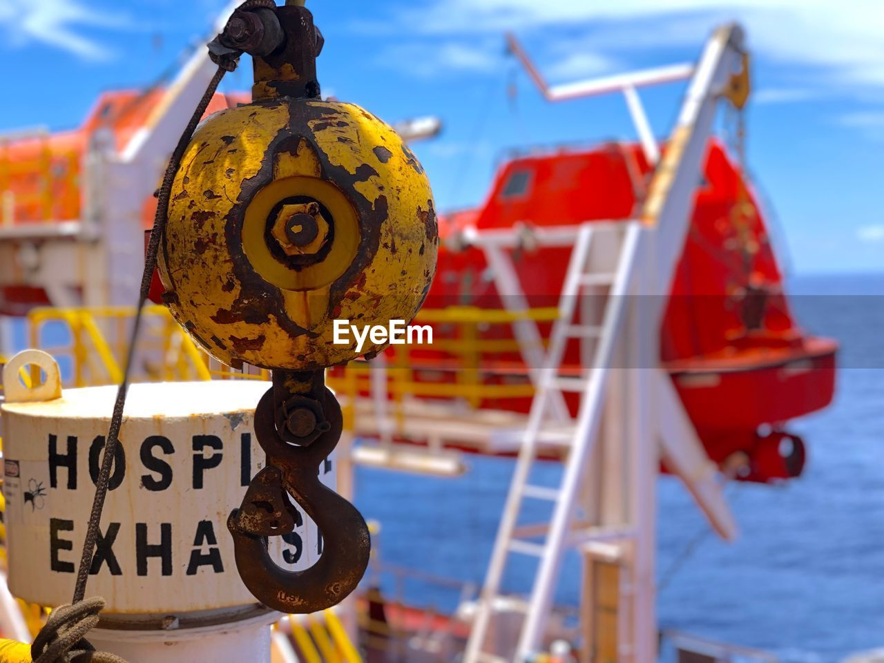 text, focus on foreground, communication, western script, no people, day, metal, close-up, transportation, outdoors, mode of transportation, sign, nautical vessel, sky, nature, red, yellow, water, architecture, hanging
