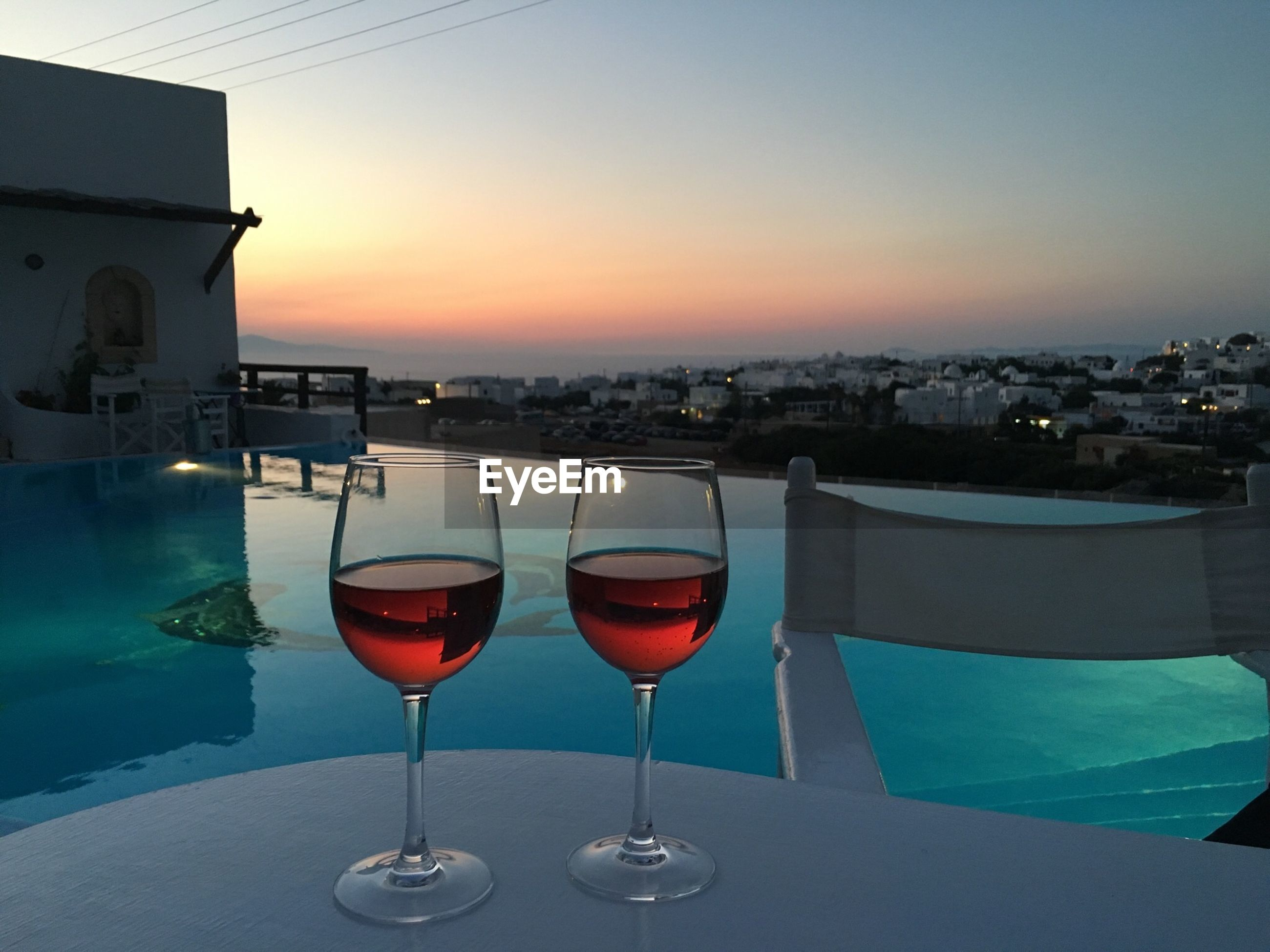 Wine glasses on table by swimming pool against sky during sunset