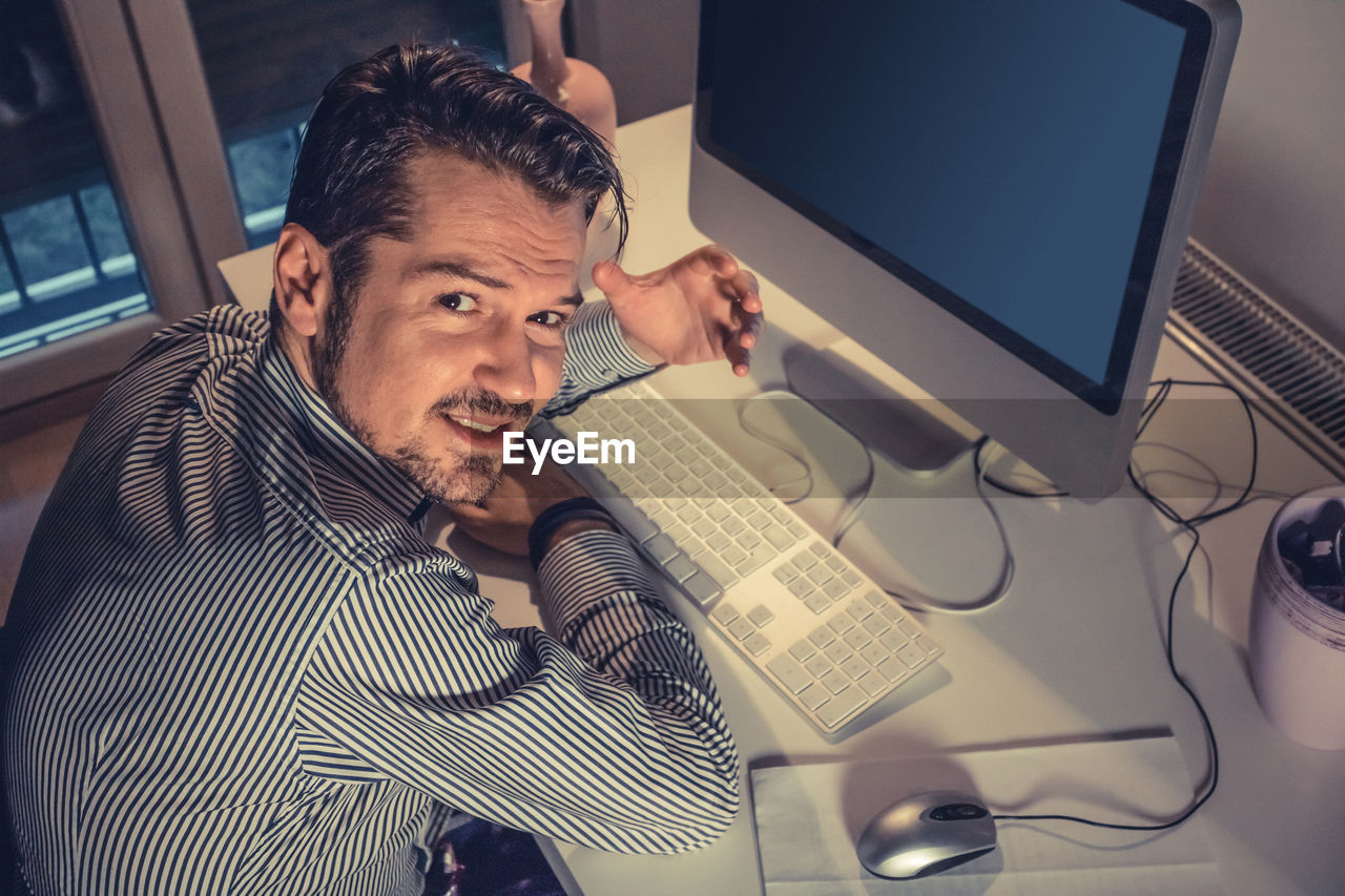 Portrait of businessman using computer in office