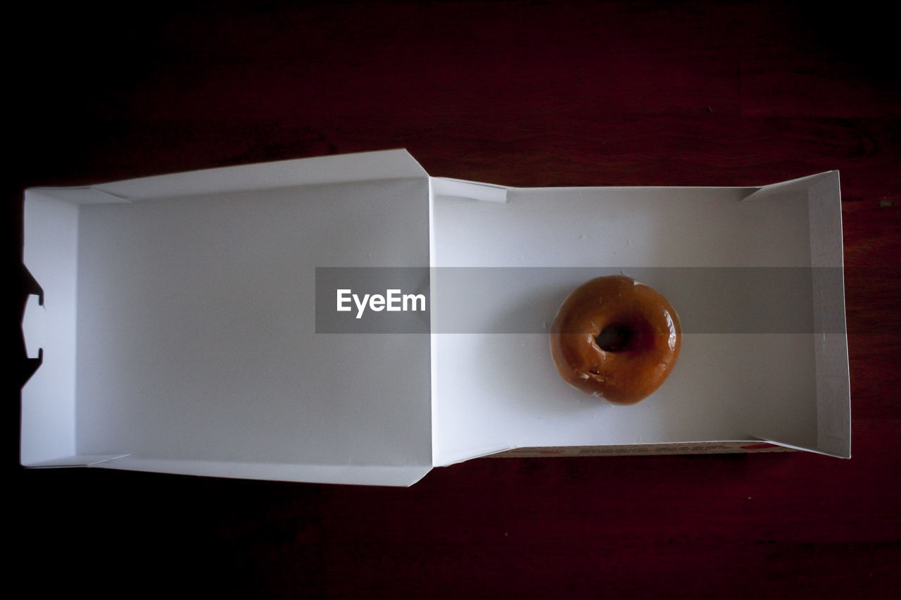 Directly above shot of donut in box on wooden table