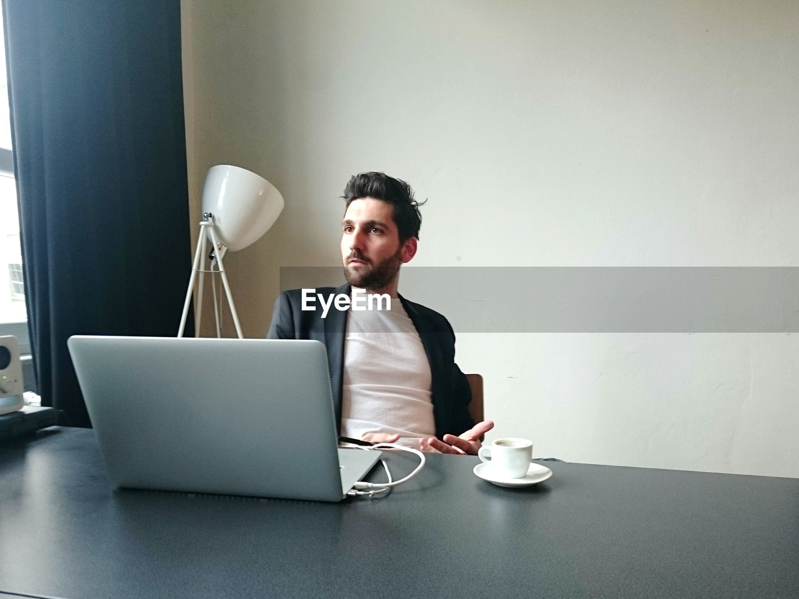 Young businessman with laptop sitting at desk in office