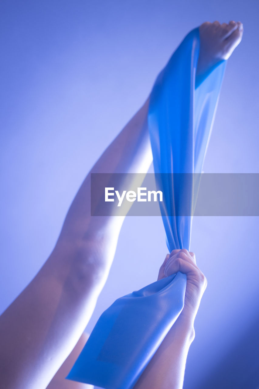 blue, hand, human hand, holding, human body part, real people, one person, finger, human finger, lifestyles, body part, unrecognizable person, women, flag, leisure activity, day, close-up, patriotism, adult, human limb, purple, blue background