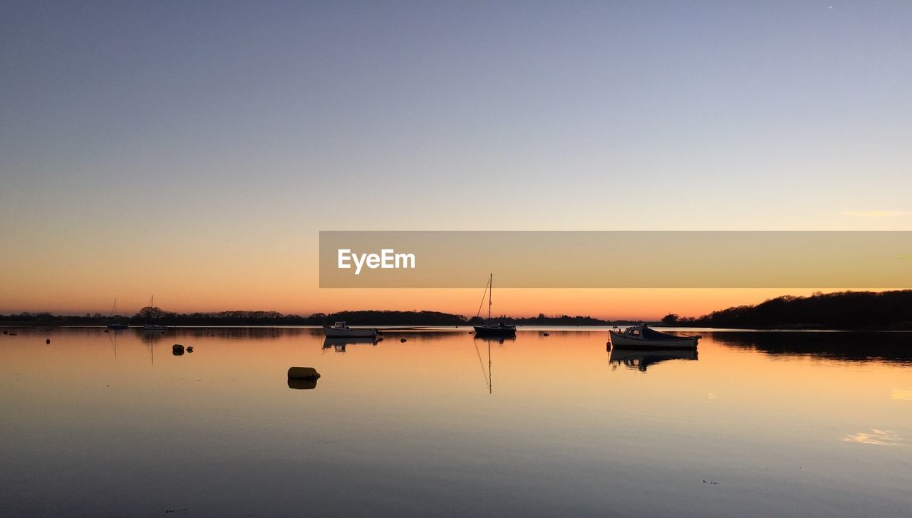 reflection, water, sunset, nature, beauty in nature, scenics, tranquility, sky, tranquil scene, nautical vessel, outdoors, transportation, no people, lake, waterfront, clear sky, day