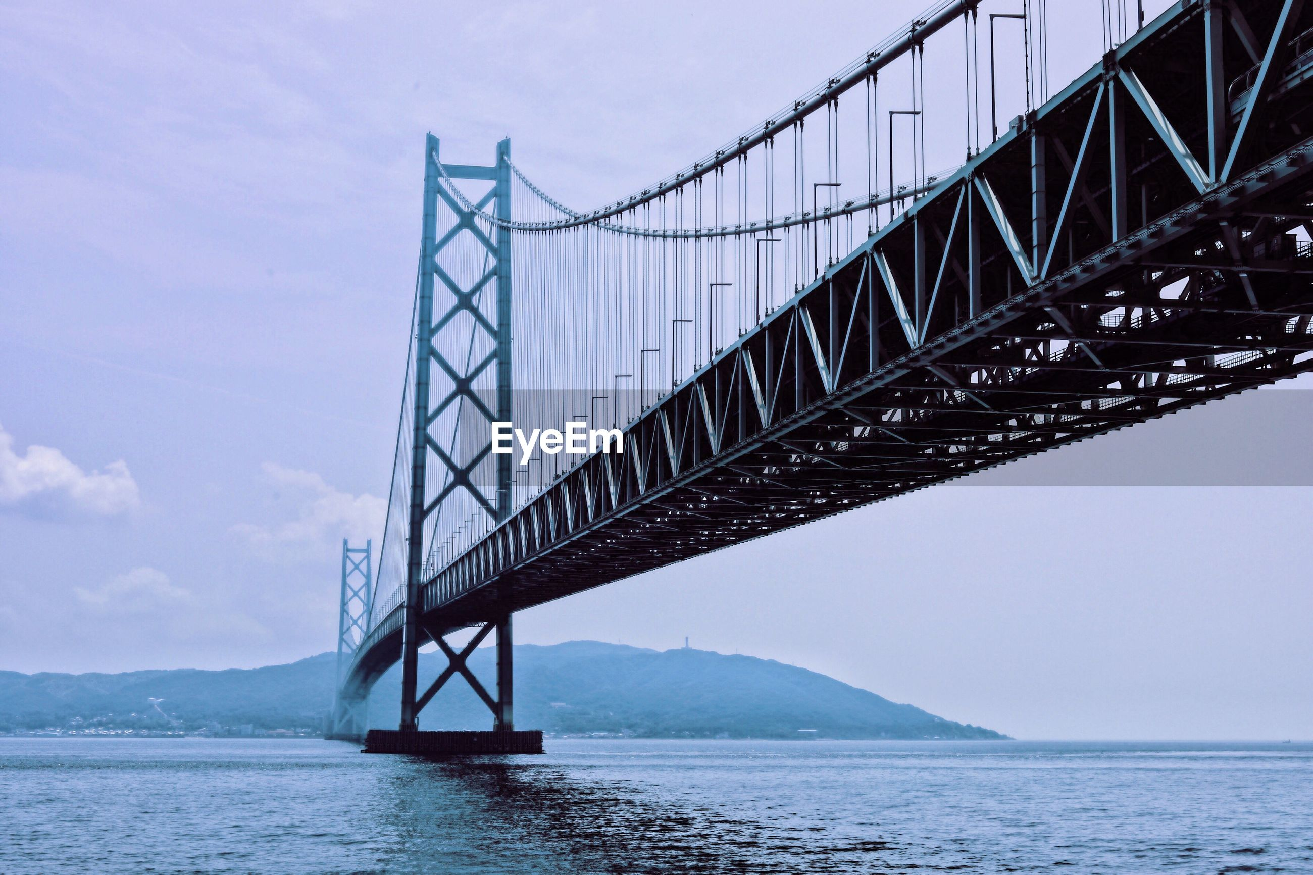 LOW ANGLE VIEW OF SUSPENSION BRIDGE IN SEA