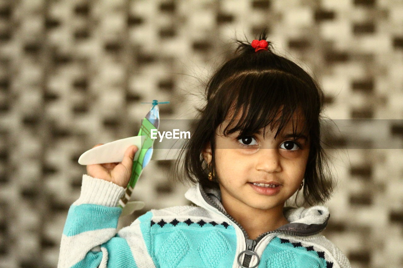 Close-up portrait of girl holding toy airplane
