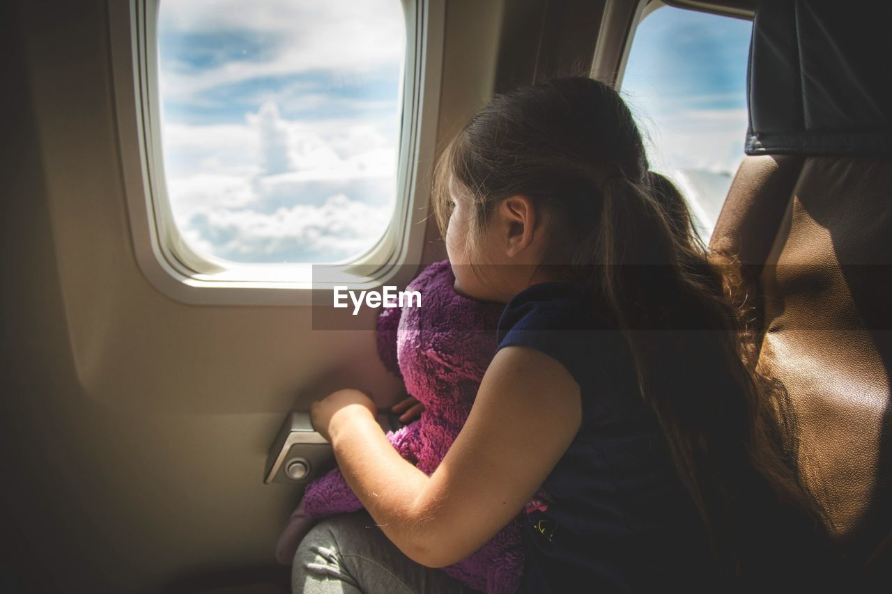 Girl sitting in airplane looking out of window