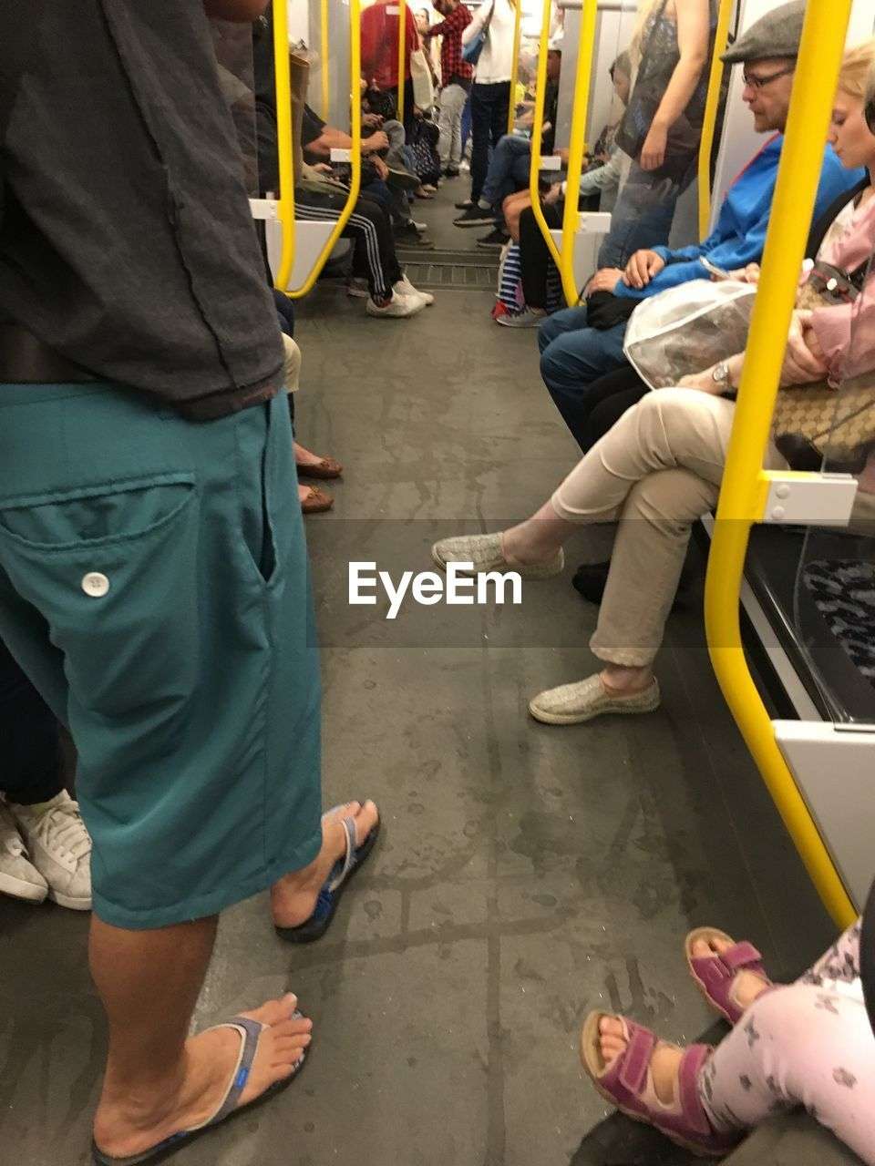 group of people, real people, men, low section, people, lifestyles, incidental people, public transportation, day, crowd, standing, sitting, women, adult, leisure activity, human leg, transportation, city, outdoors