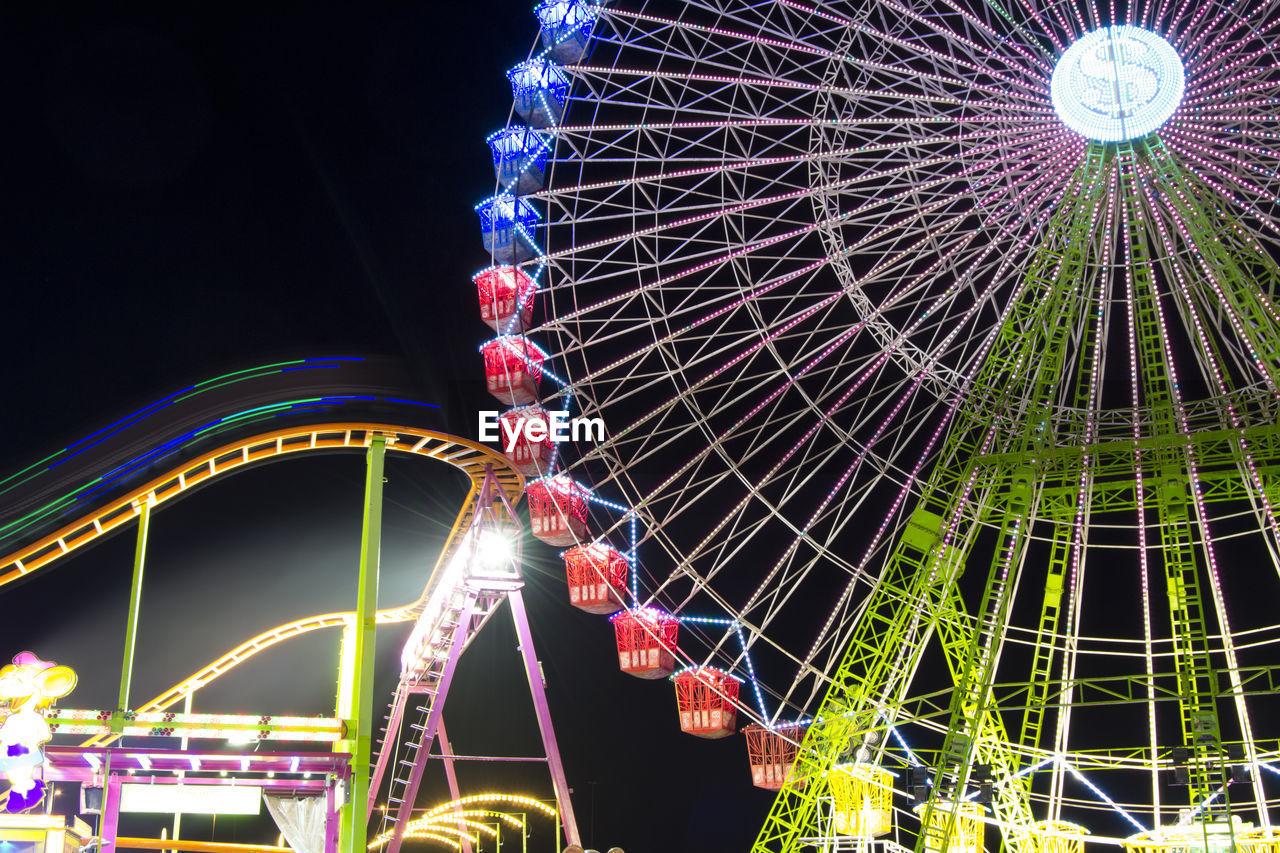 arts culture and entertainment, amusement park, night, amusement park ride, ferris wheel, fairground, fairground ride, illuminated, low angle view, big wheel, leisure activity, ride, outdoors, no people, clear sky, sky, multi colored, architecture