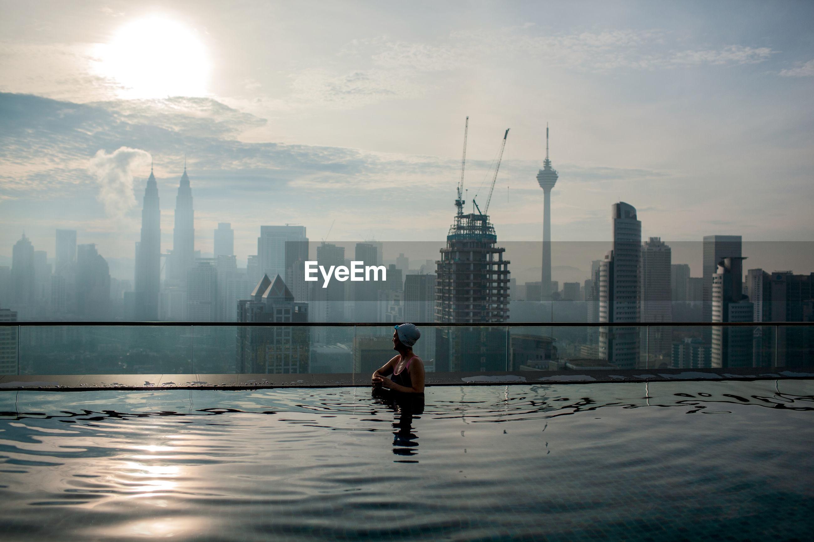MAN IN SWIMMING POOL BY BUILDINGS AGAINST SKY