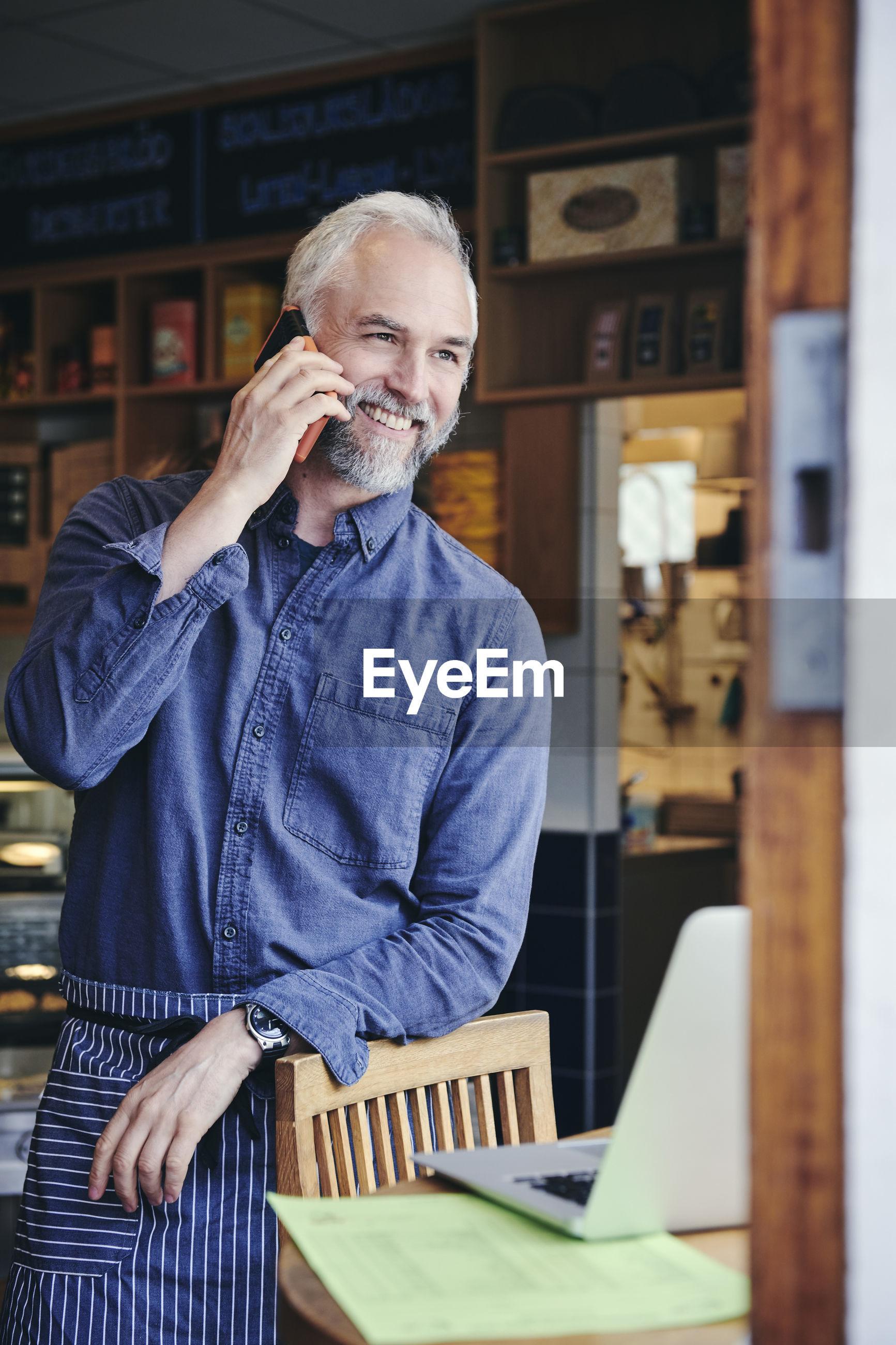 MAN USING MOBILE PHONE IN LAPTOP