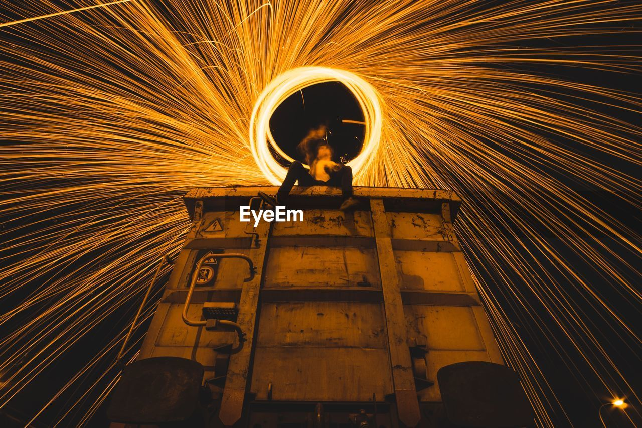 Low angle view of person sitting on train while spinning fire steel wool at night