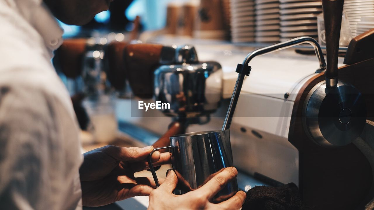 Midsection Of Man Holding Mug By Espresso Maker At Cafe