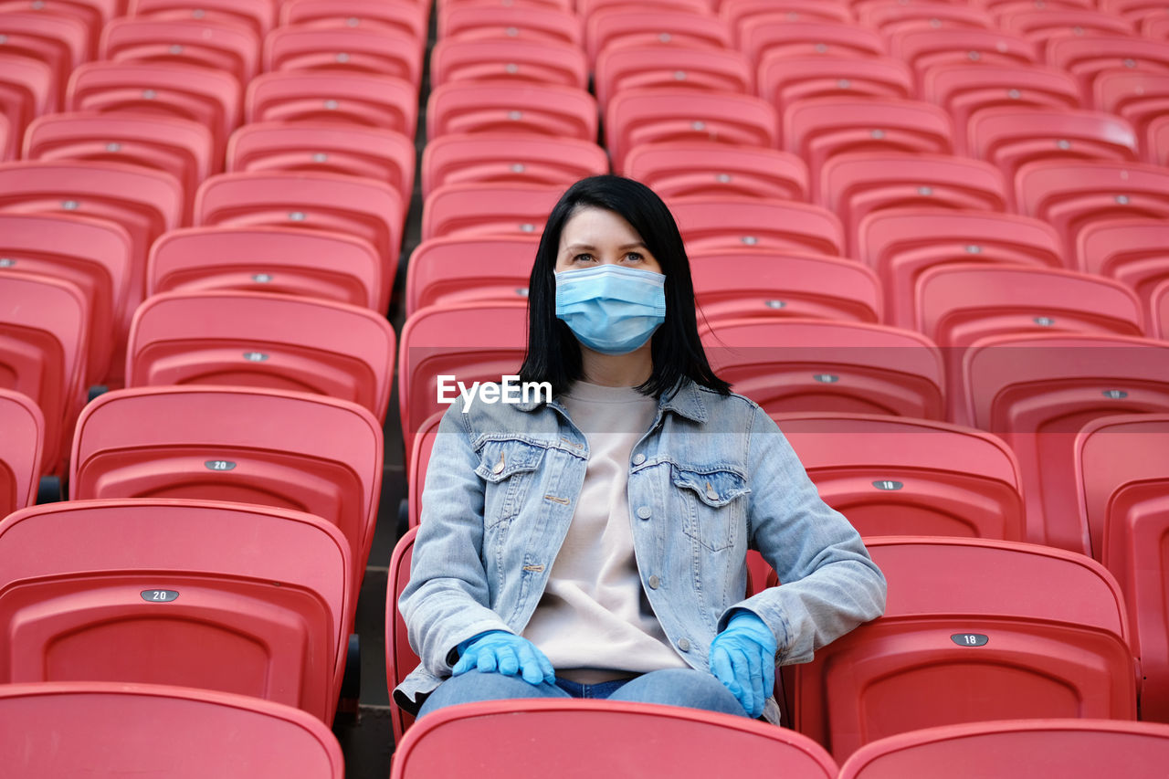 FULL LENGTH PORTRAIT OF WOMAN SITTING ON CHAIR IN STADIUM