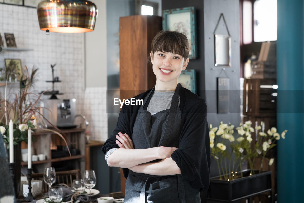 PORTRAIT OF A SMILING YOUNG WOMAN STANDING IN FRONT OF OFFICE