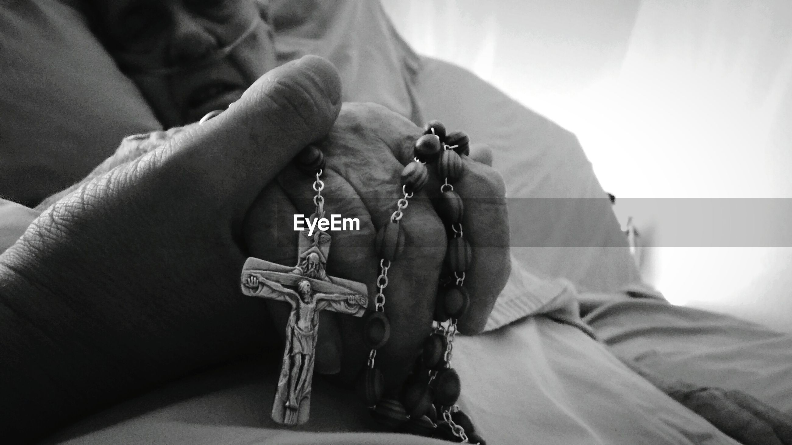 Close-up of hands holding rosary