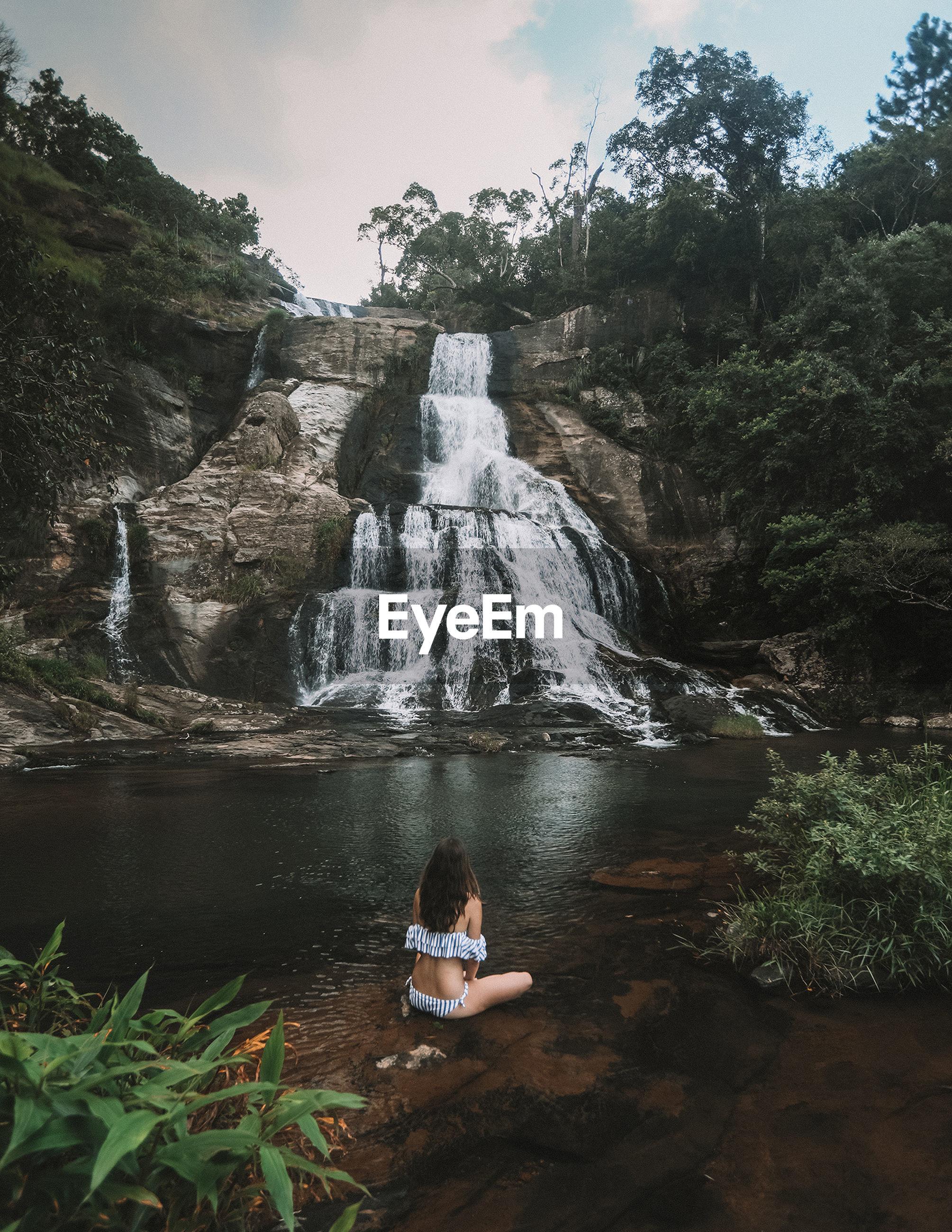 Woman sitting on rock against diyaluma falls