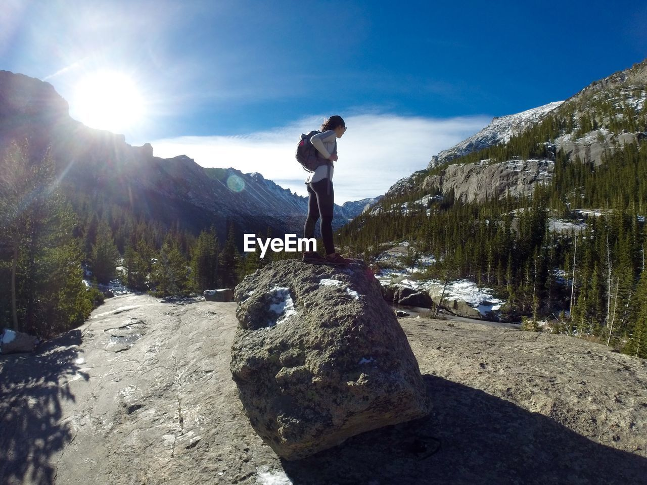 Side View Of Hiker Standing On Rock Against Mountains On Sunny Day
