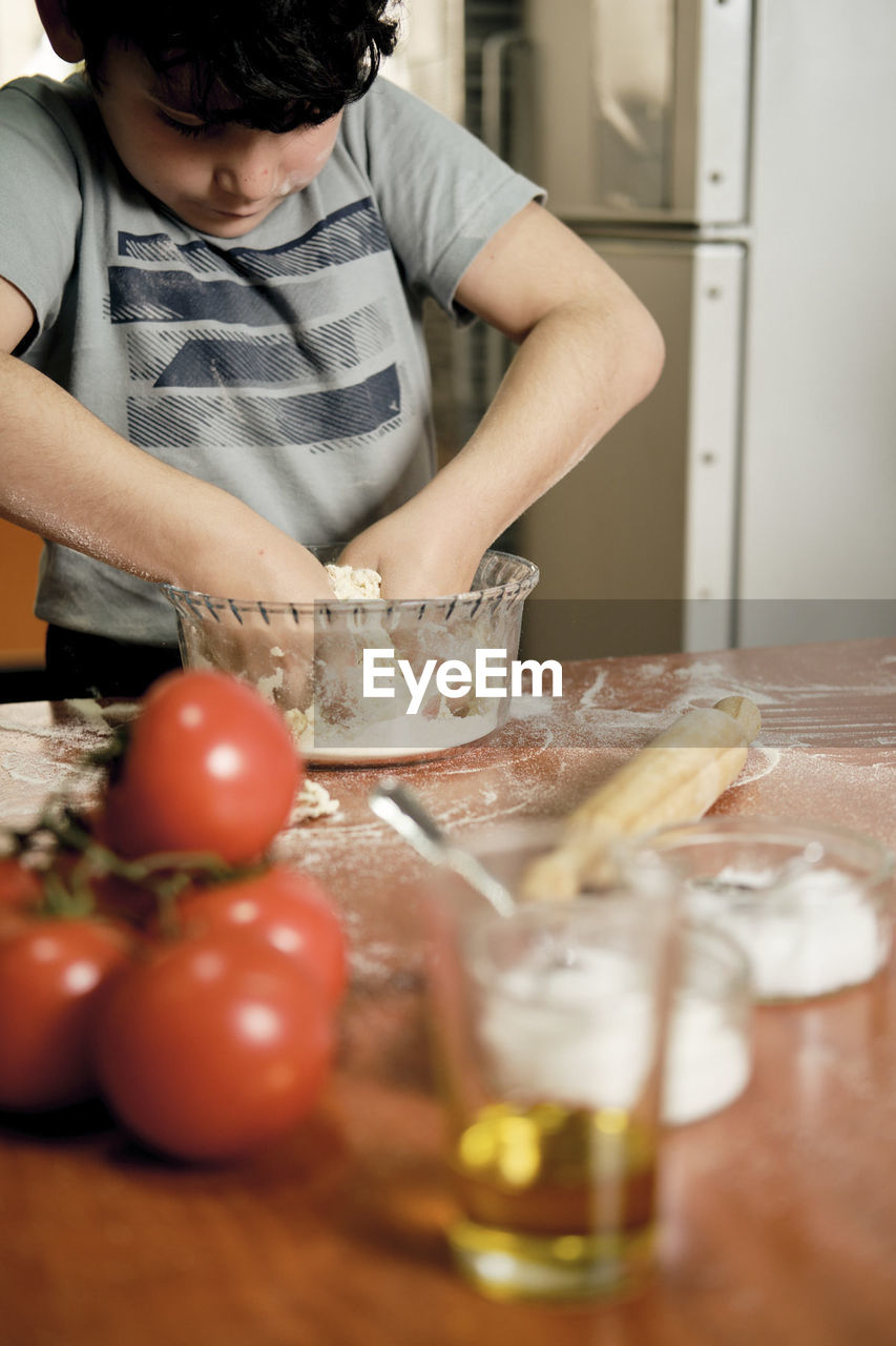MIDSECTION OF MAN HOLDING FOOD AT HOME