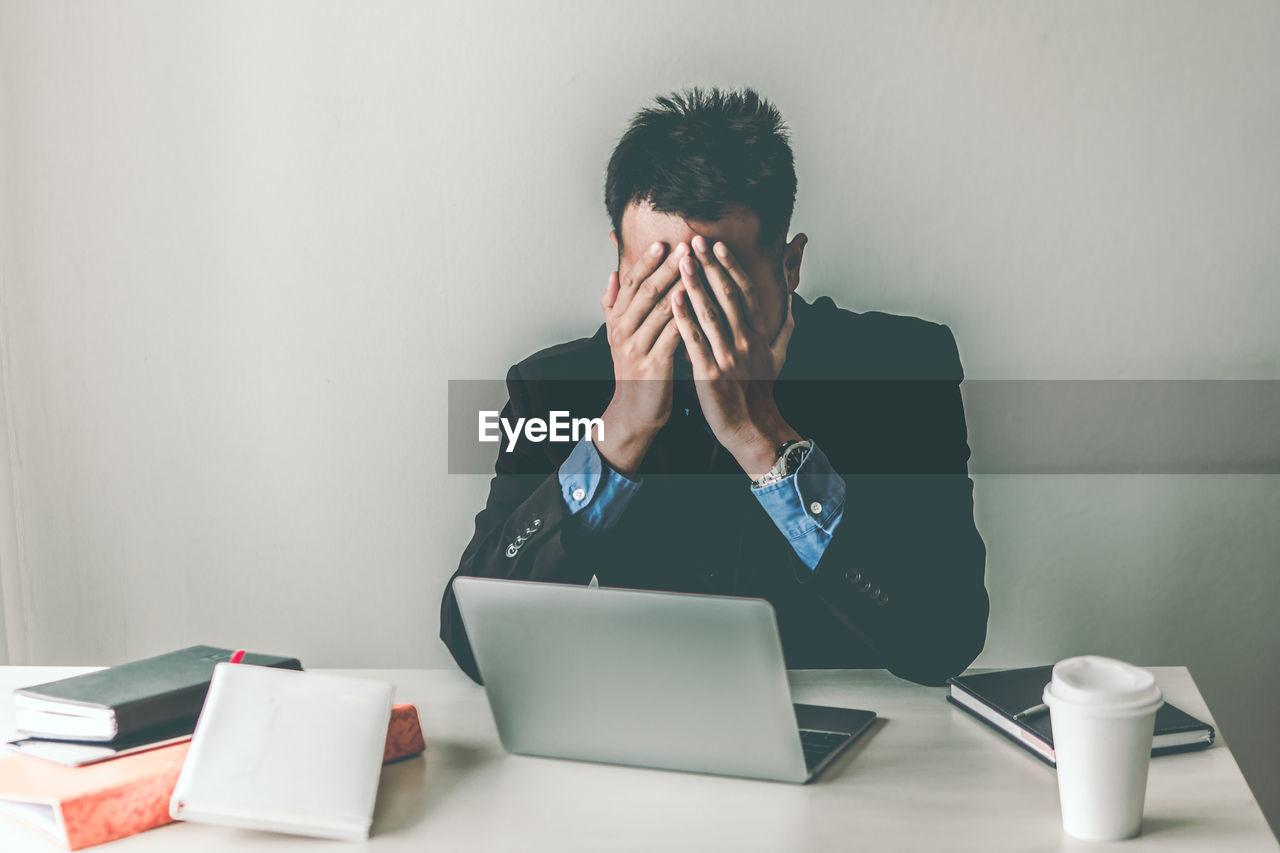 Frustrated businessman covering face while sitting on table