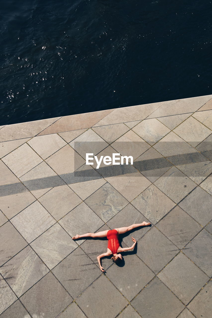 high angle view, water, one person, full length, red, nature, day, real people, outdoors, motion, lifestyles, sea, leisure activity, sunlight, flooring, rear view, childhood, shadow, swimming pool