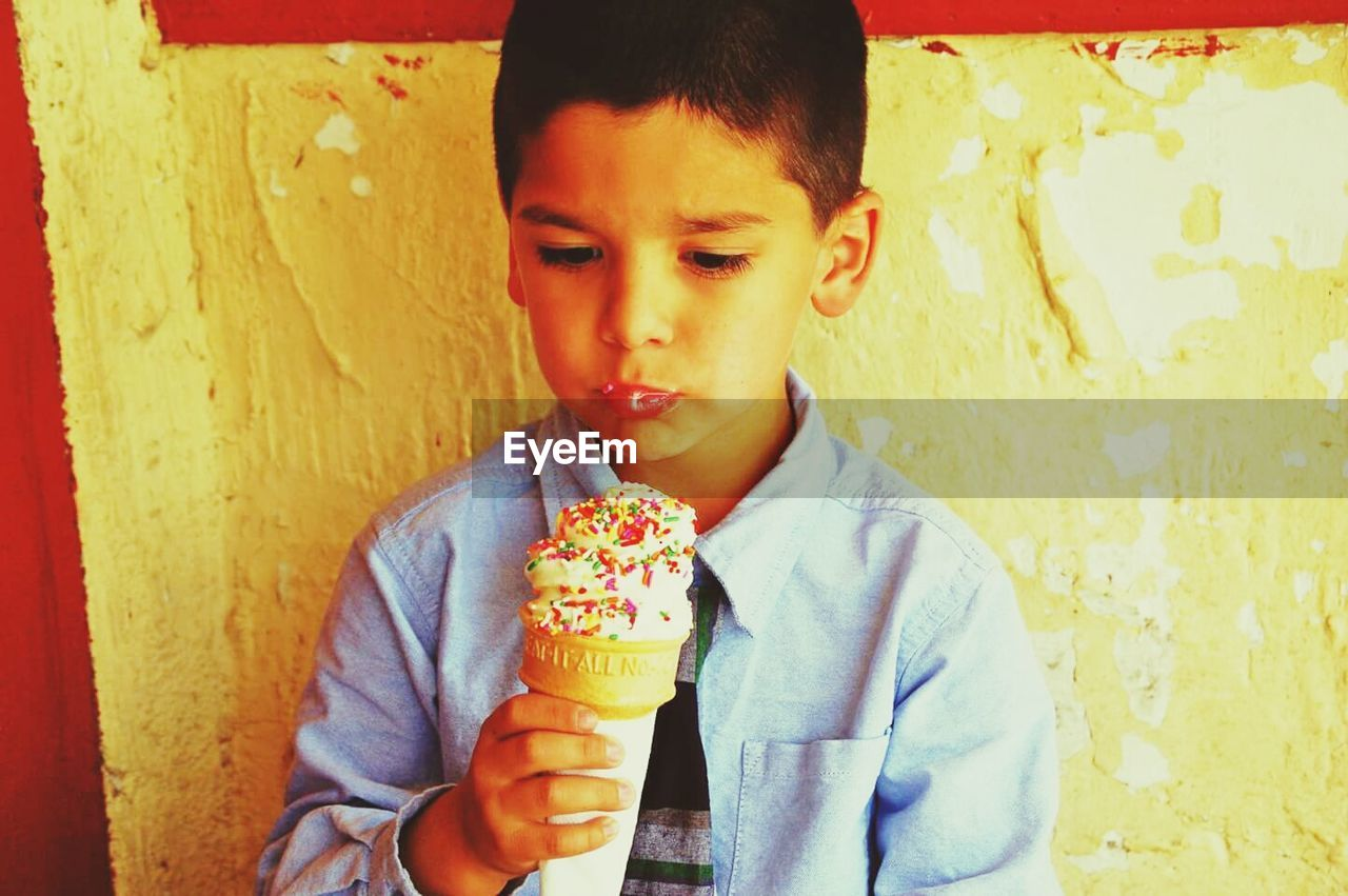 childhood, boys, real people, one person, front view, ice cream, outdoors, casual clothing, day, food and drink, leisure activity, holding, lifestyles, elementary age, frozen food, headshot, sweet food, ice cream cone, portrait, food, close-up, one boy only, freshness, people