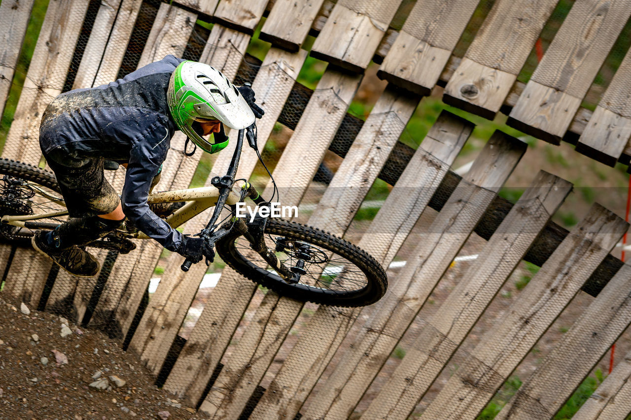bicycle, transportation, one person, real people, men, day, mode of transportation, helmet, wood - material, lifestyles, land vehicle, headwear, leisure activity, full length, activity, outdoors, high angle view, riding, skill, wheel, tire