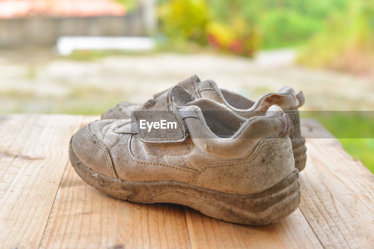 Close-up of old shoes on wooden table