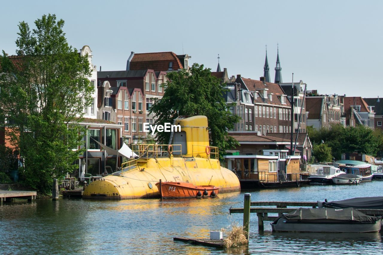 Submarine at riverbank with residential buildings in background