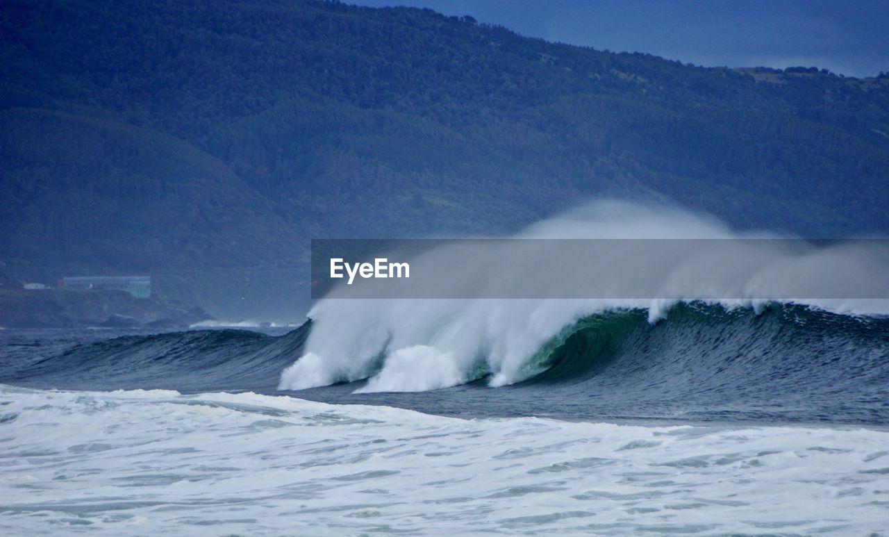 WAVES SPLASHING ON SEA AGAINST MOUNTAIN