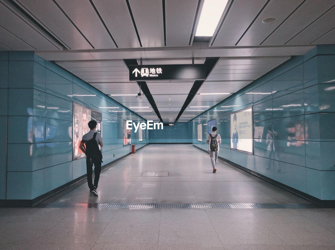 Rear View Of Men Walking On Walkway At Subway Station