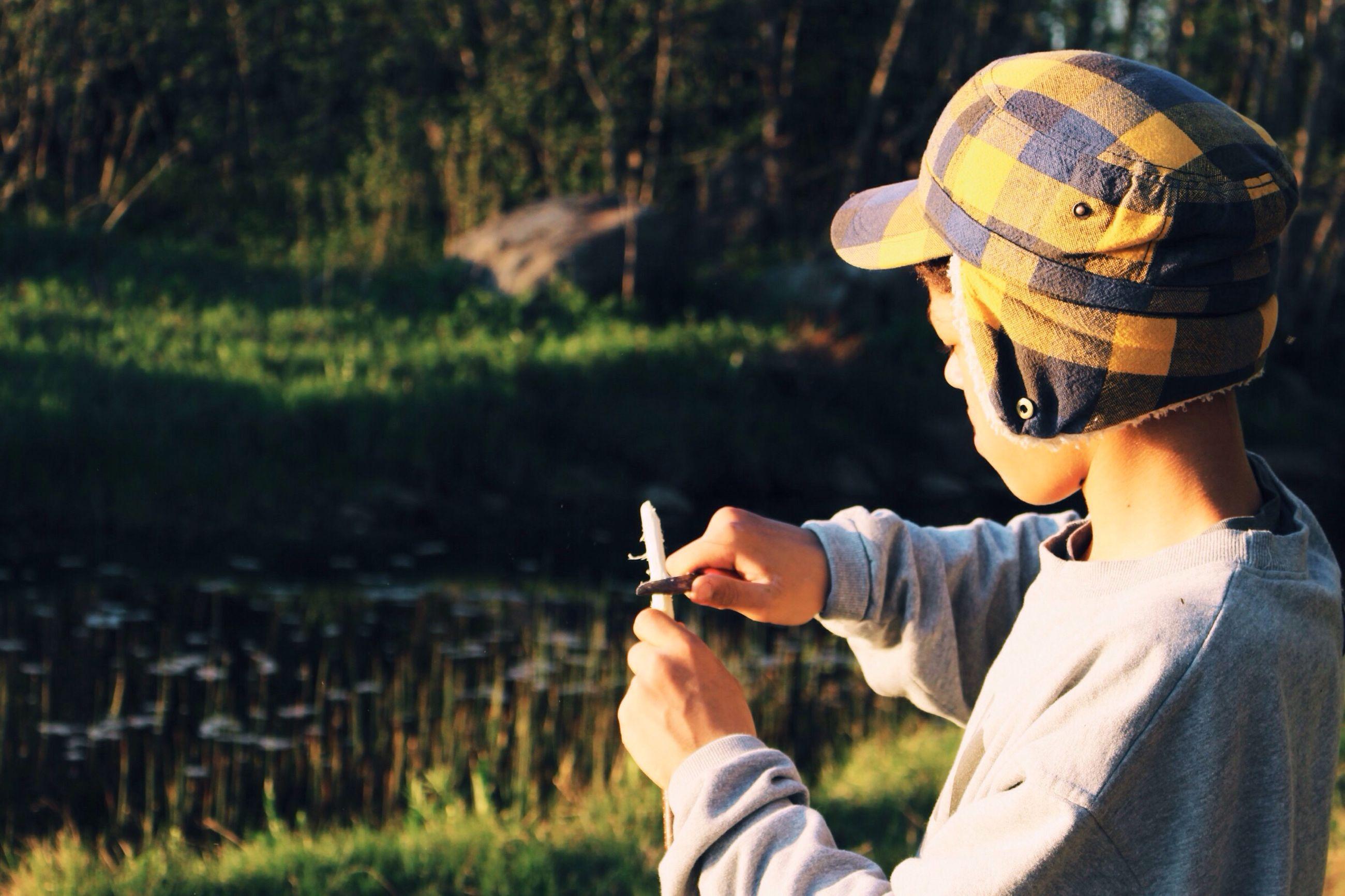 Boy cutting stick outdoors