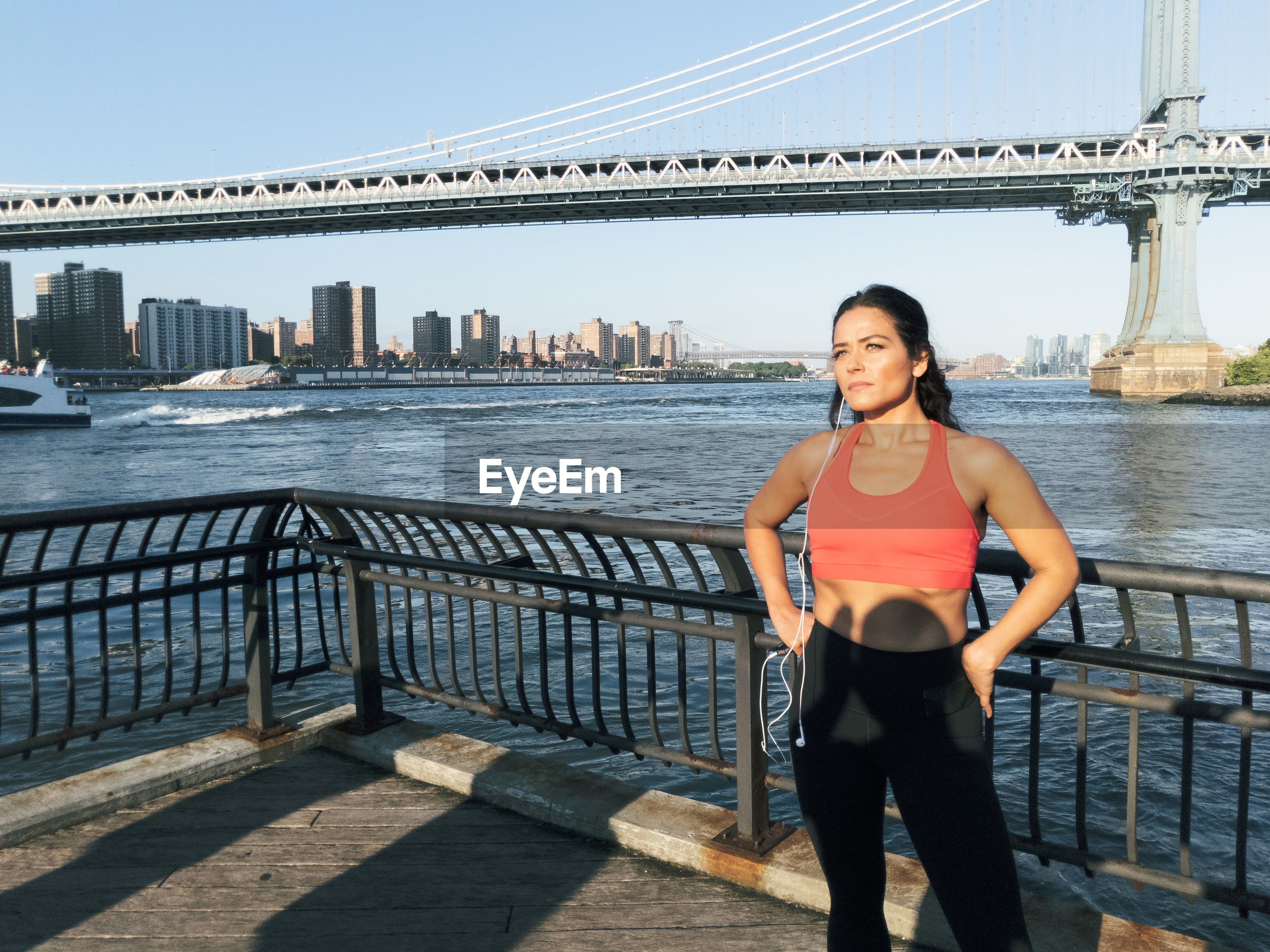 Young woman exercising on footpath against bridge in city
