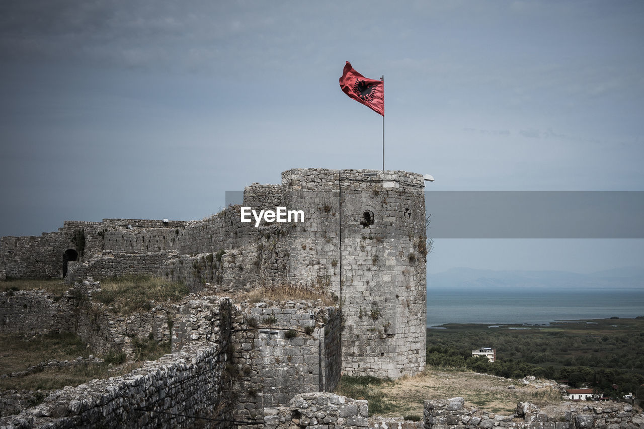 Low angle view of albanian flag on old ruin against sky