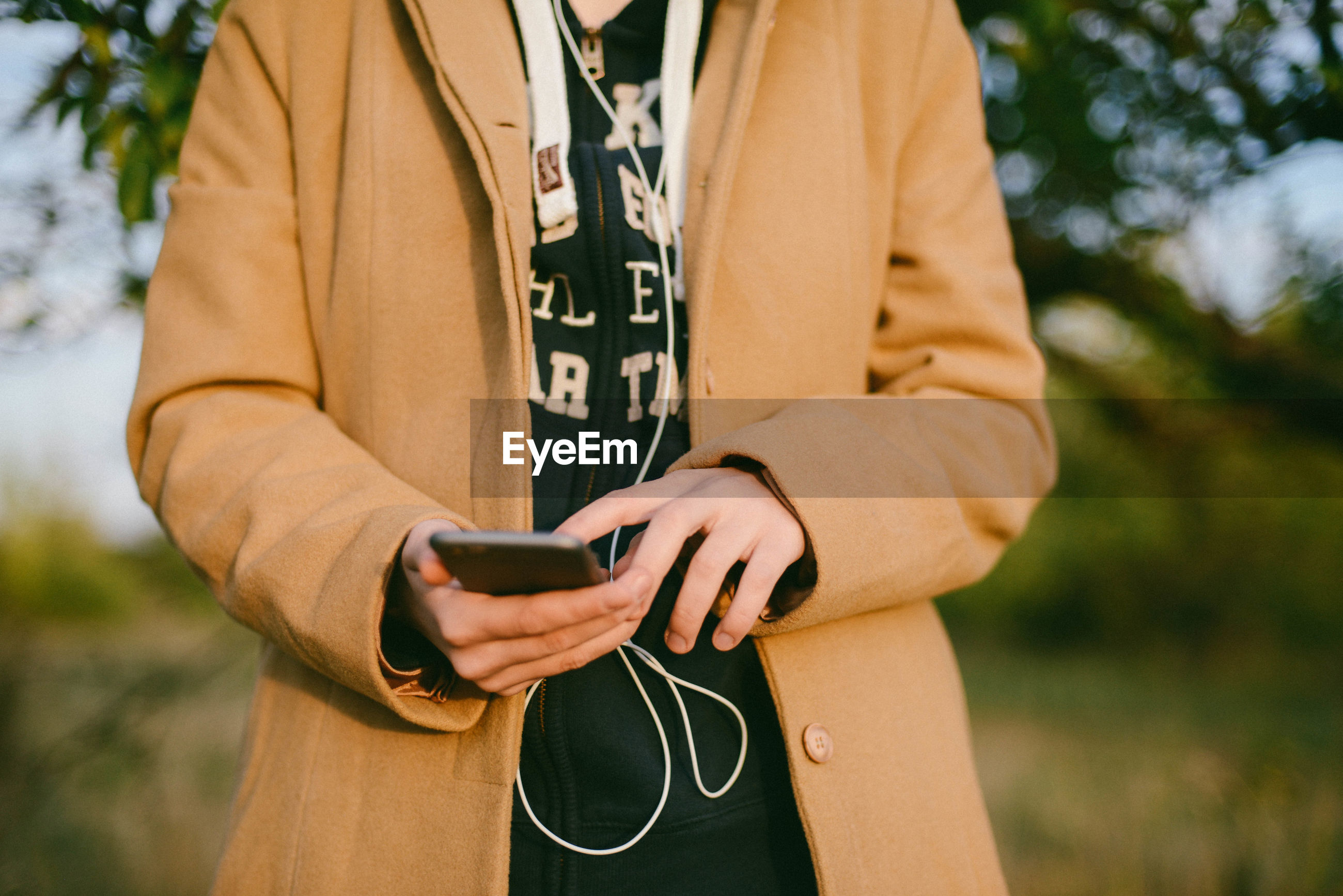 Midsection of woman using phone while standing outdoors