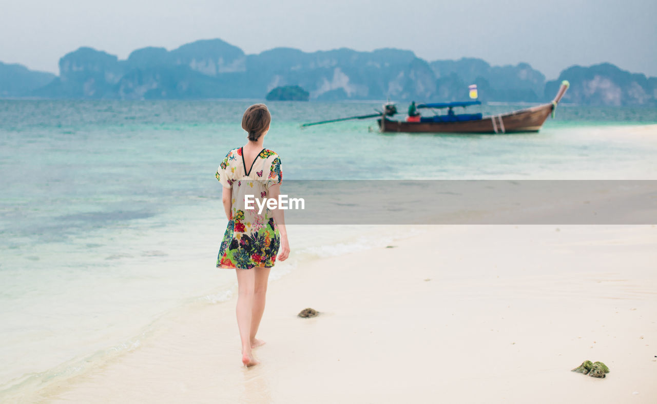 Woman Walking On Sea Shore By Moored Longtail Boat At Beach