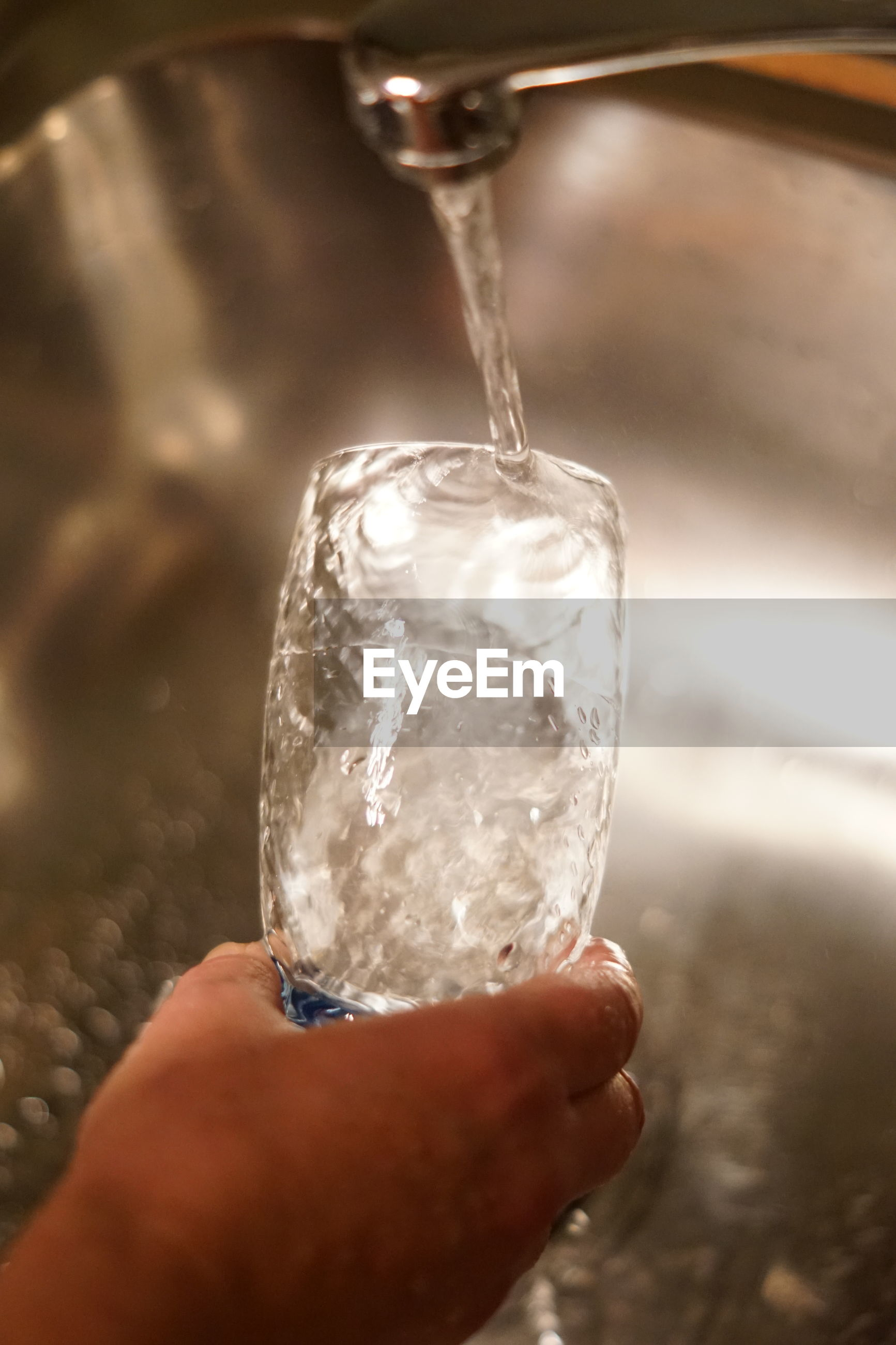 Cropped hand of person washing drinking glass in kitchen