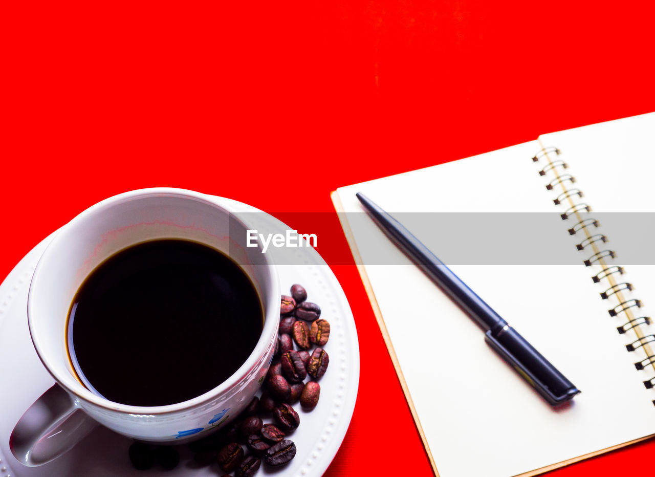 food and drink, cup, drink, refreshment, mug, coffee cup, coffee - drink, coffee, red, high angle view, still life, table, indoors, crockery, book, close-up, no people, black coffee, publication, saucer, note pad, black tea, tea cup, blank