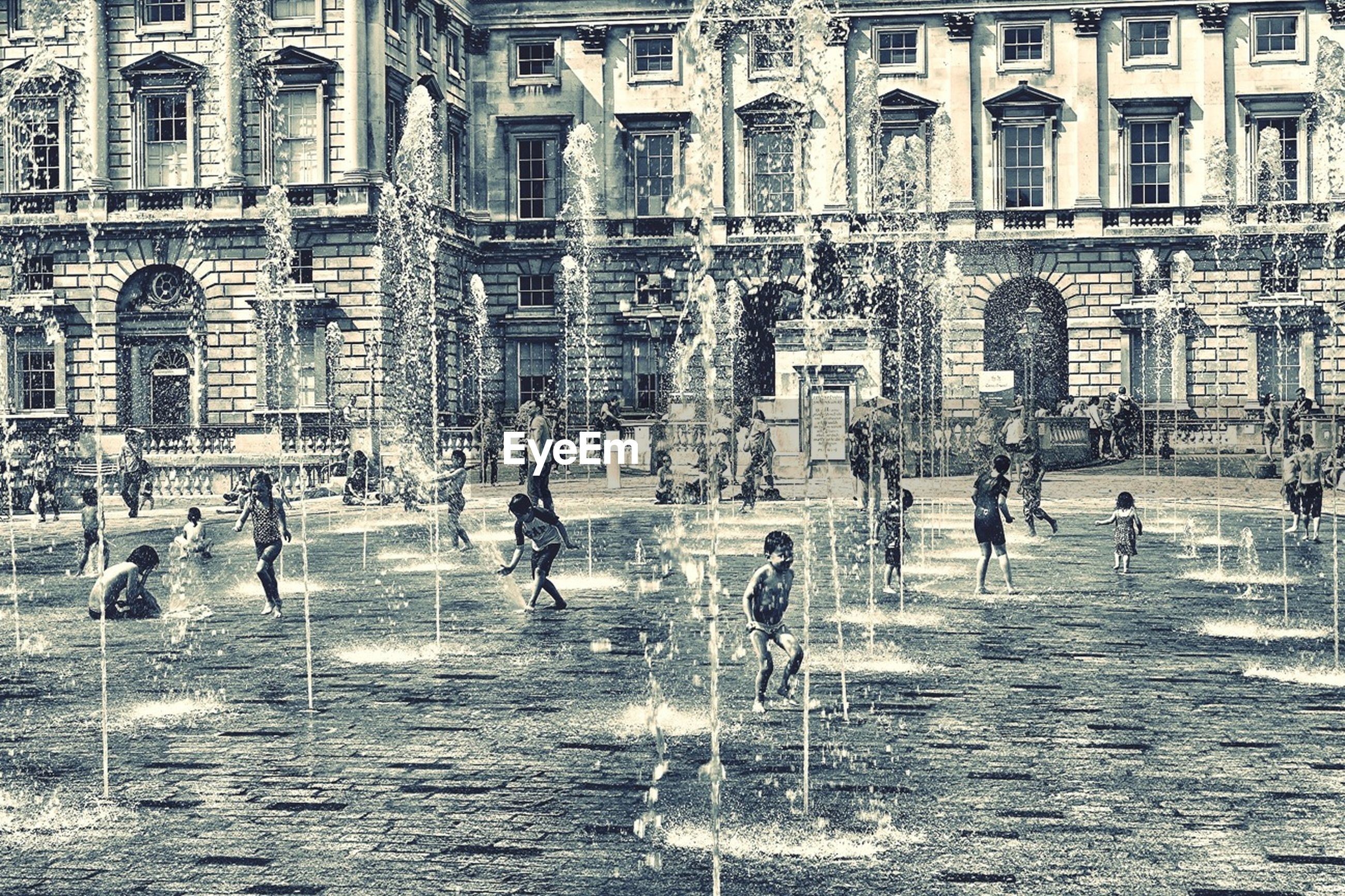 architecture, building exterior, built structure, large group of people, lifestyles, fountain, person, men, leisure activity, water, walking, tourist, city, city life, mixed age range, motion, town square, tourism, travel destinations