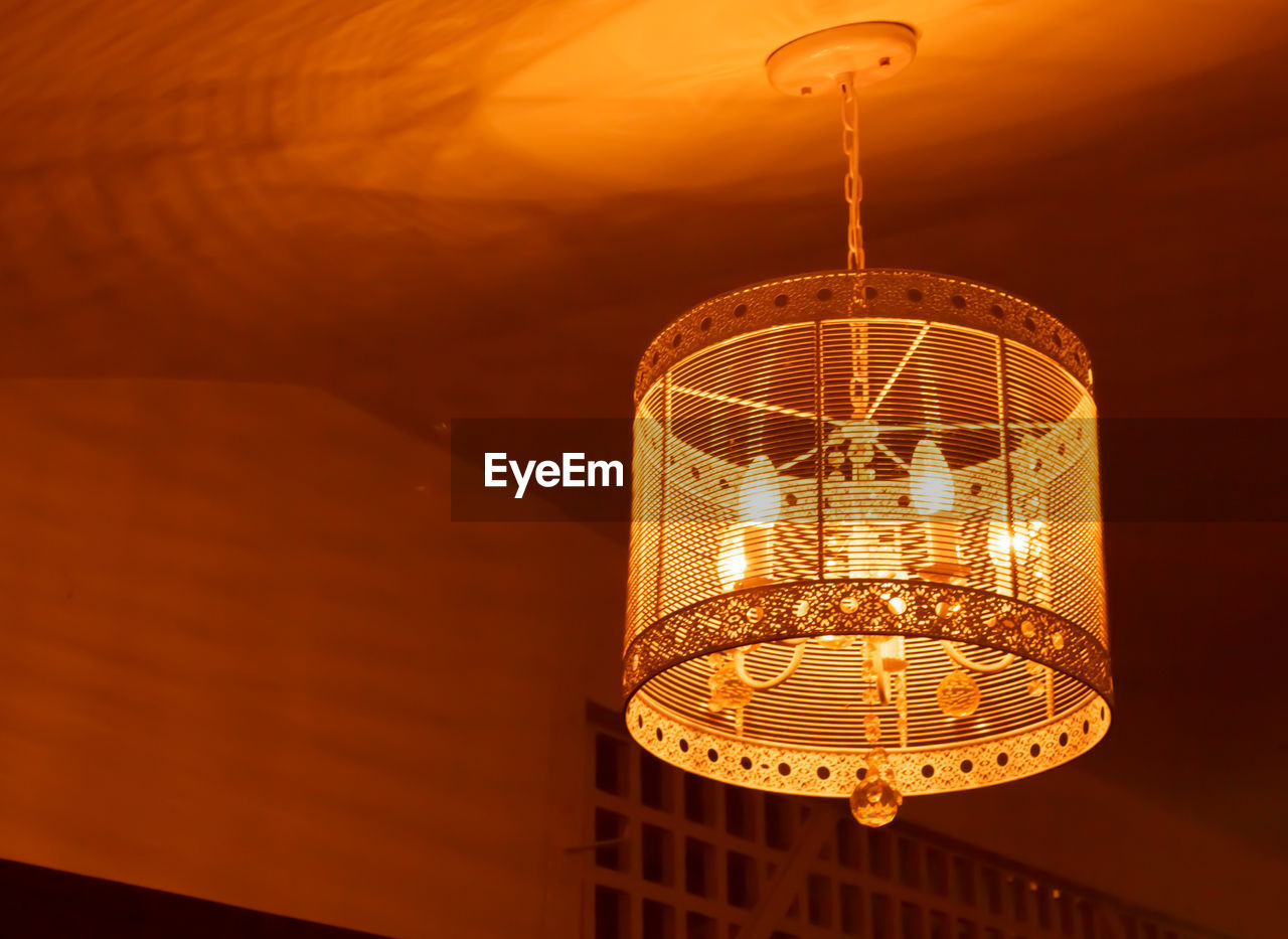 illuminated, lighting equipment, focus on foreground, low angle view, hanging, orange color, no people, architecture, indoors, decoration, built structure, glowing, night, ceiling, light - natural phenomenon, sunset, pendant light, close-up, electricity, luxury