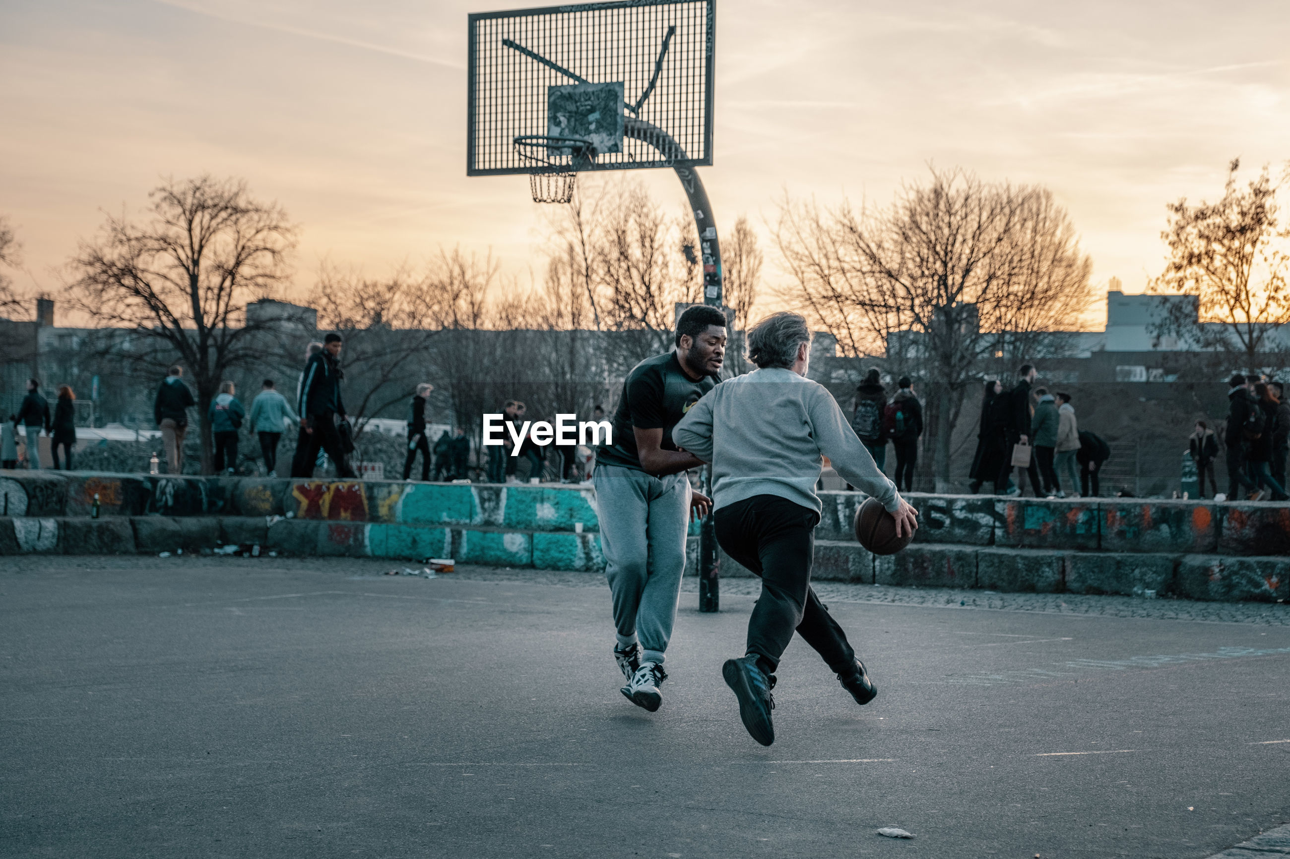 MEN PLAYING BASKETBALL ON CITY
